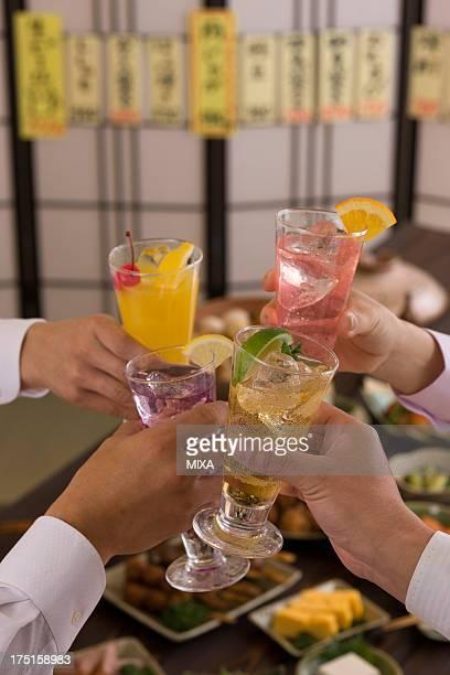 Four People Toasting with Various Cocktails at Izakaya
