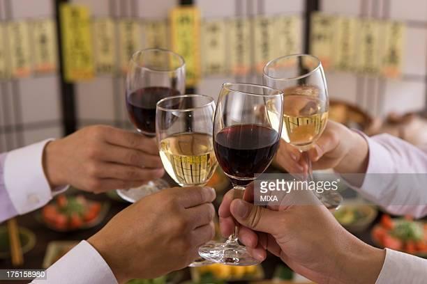 Four People Toasting with Wine at Izakaya