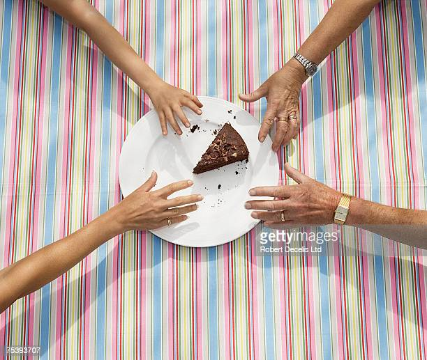 Four people trying to grab last piece of cake, elevated view