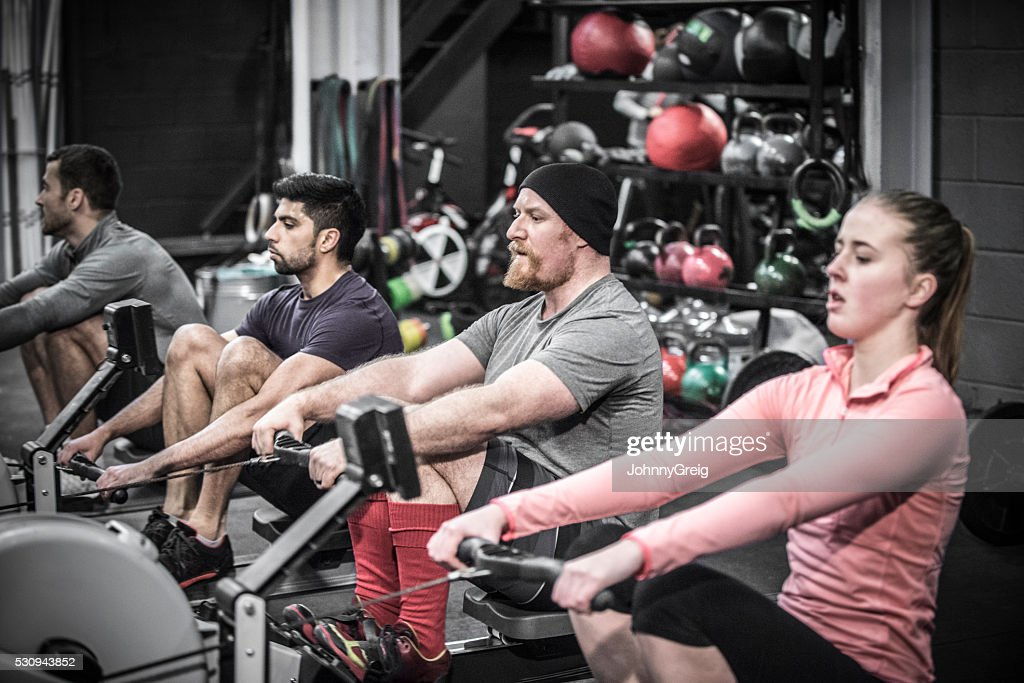 Four people using rowing machines in cross training class. : Stock Photo