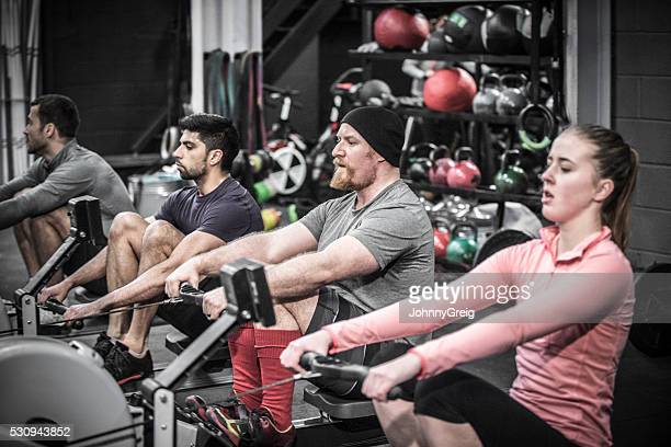 four people using rowing machines in cross training class. - circuit training stock photos and pictures