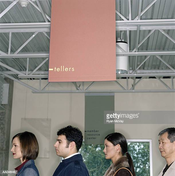 Four people waiting in line at bank, side view, close-up