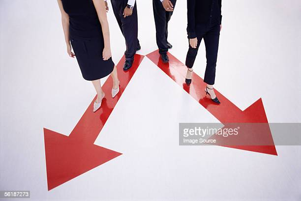four people walking along arrow signs - following arrows stock pictures, royalty-free photos & images