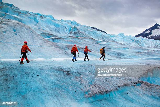 Four people walking on Mendenhall Glacier, Alaska, USA