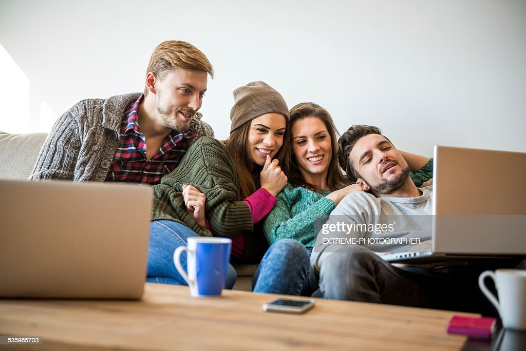 Four people watching multimedia content : Stock Photo