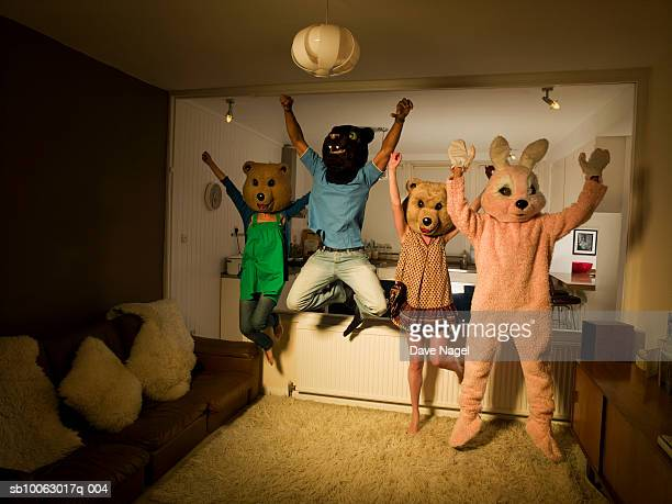 Four people wearing animal costumes and masks in room, jumping