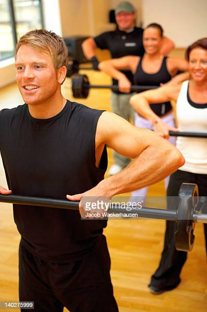 Four people weight training in fitness center