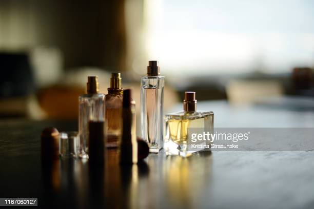 four perfume bottles anad red lipstick in a beautiful sunlight - perfume stock pictures, royalty-free photos & images