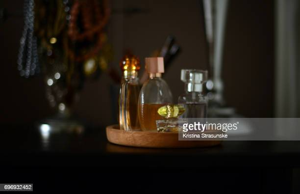 four perfume bottles in a perfume tray on a table