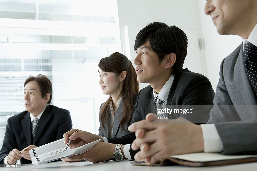 BUSINESS SCENE Four persons in a meeting : ストックフォト