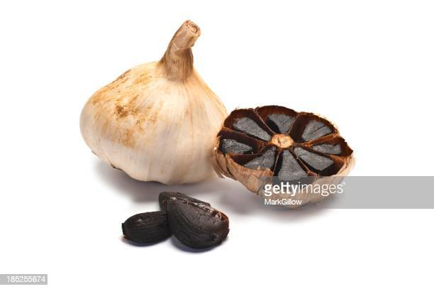 Four Pieces of black garlic in various stages of preparation