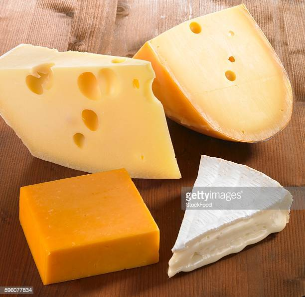 Four pieces of cheese (Emmentaler, Gouda, Cheddar and Brie)