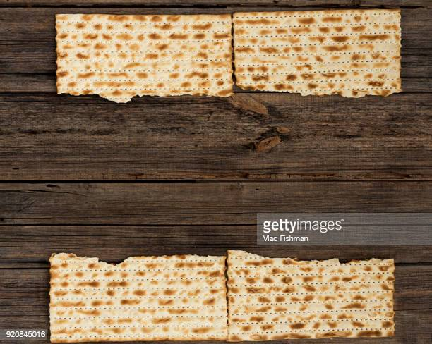 Four pieces of matzah on a vintage wood background with copy space or text space.