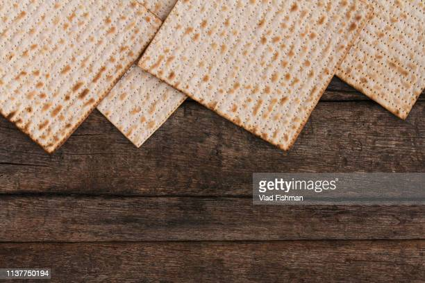 four pieces of matzah or matza on a vintage wood background with copy space or text space - passover symbols stock pictures, royalty-free photos & images