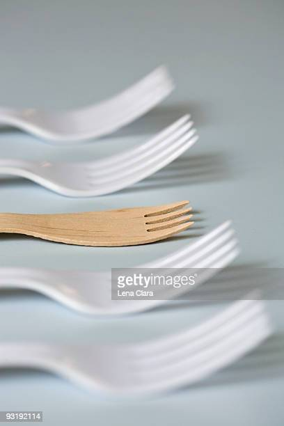 Four plastic forks and one wooden fork