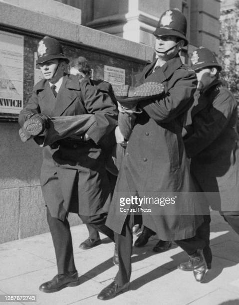 Four police officers carry, each officer holding a limb, at an anti-fascist demonstration picketing the annual general meeting of the National Front,...