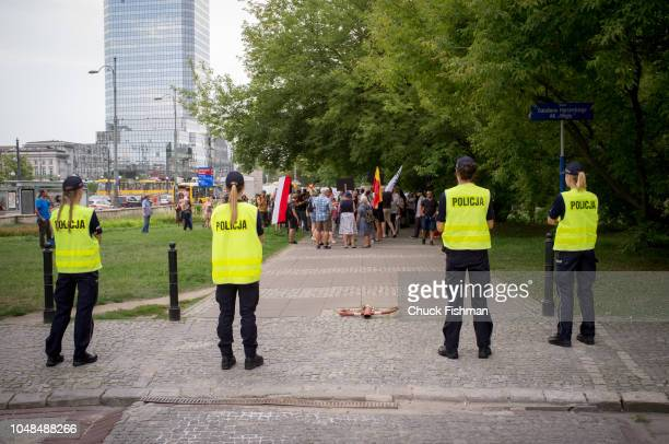 Four police officers watch protesters during a rally against police violence Skwer Batalionu Harcerskiego Warsaw Poland August 8 2018 The square is...