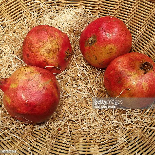 four pomegranates in a wicker basket - jean marc payet stockfoto's en -beelden