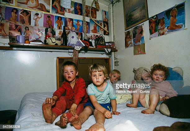 Four poverty stricken white South African children with dirty faces and clothing sit on a bed in their Johannesburg home Pornographic photographs...