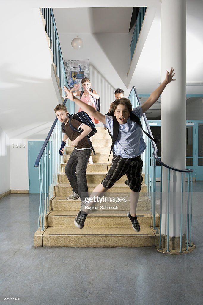 Four pre-adolescent children running down stairs excited : Stock Photo