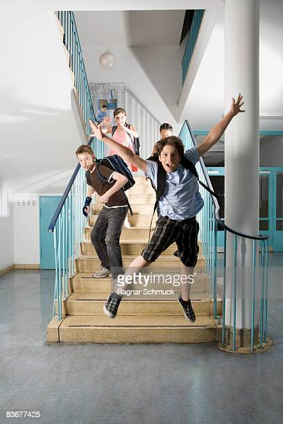 Four pre-adolescent children running down stairs excited