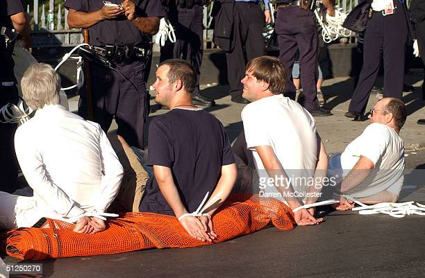 Four protesters sit on the ground following their arrest at the corner of Fulton and Church Streets as they attempted to march from Ground Zero to...