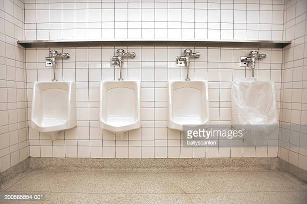 Four public urinals, one covered with clear plastic