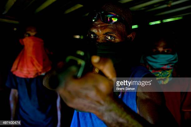 Four Raskol gang members and a handmade gun photographed in the impoverished eight mile settlement in Port Moresby Papua New Guinea 23 December 2008...