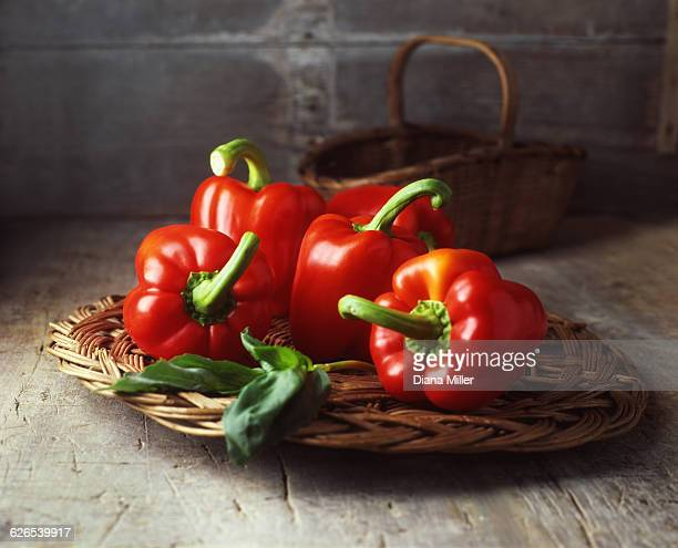 Four red peppers on vintage wicker basket