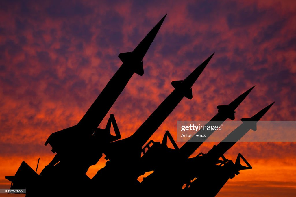 Four rockets of anti-aircraft missile system are directed upwards against the background of sunset : Stockfoto