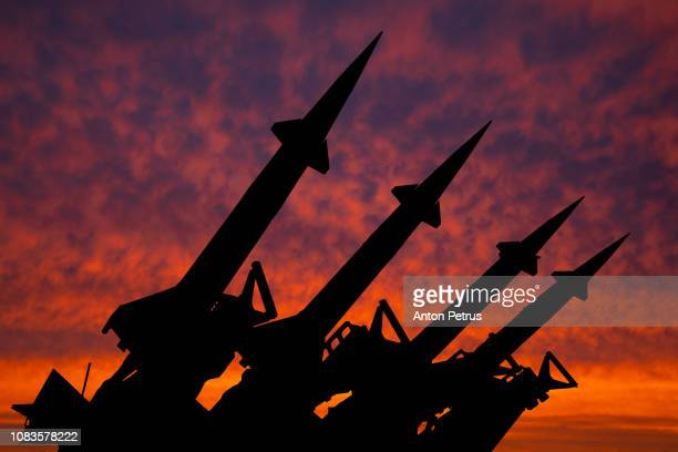 four rockets of anti-aircraft missile system are directed upwards against the background of sunset - armi foto e immagini stock
