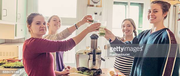 "four roommates toasting with green juice in their appartement kitchen. - ""martine doucet"" or martinedoucet stock pictures, royalty-free photos & images"