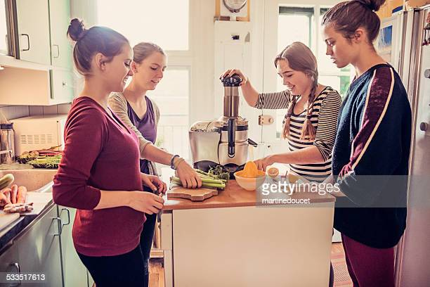 Four roommates using a juicer in their appartement kitchen.