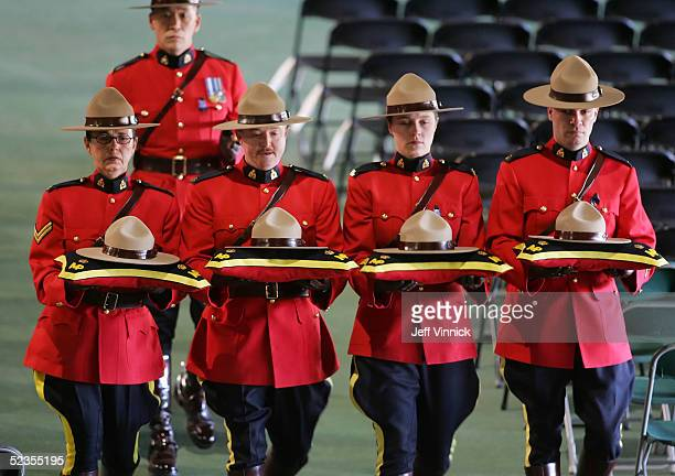 Four Royal Canadian Mounted Police officers carry the hats of four officers who were murdered last week during a rehearsal for a memorial service...