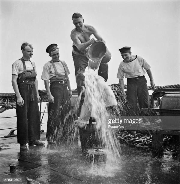 Four Royal Navy sailors give a shipmate a shower bath on the deck of the W-class destroyer HMS Whitshed during convoy escort duty off the English...