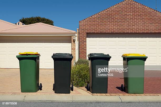 Four rubbish bins lined up on a suburban pavement