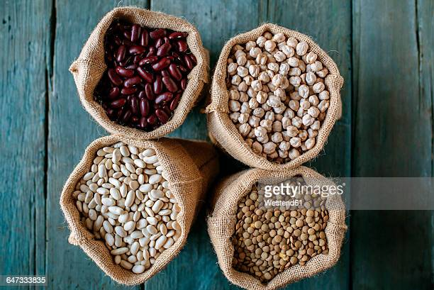 Four sacks of dried brown lentils, chickpeas and red and white beans on wood