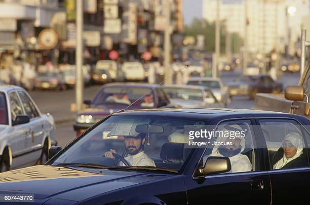 Four Saudi friends ride in a car on a busy street filled with traffic