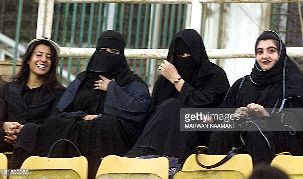 Four Saudi women attend a soccer match opposing Saudi Arabia's alShabab to Kuwait's Salmieh teams 28 September 1999 during the Arab Clubs...