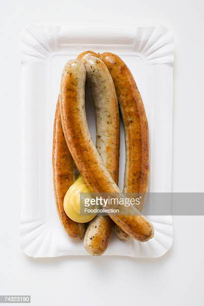 Four sausages with mustard