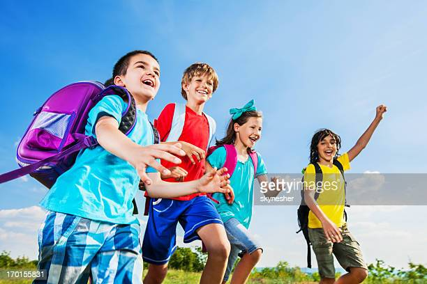 Four school children running in the nature.