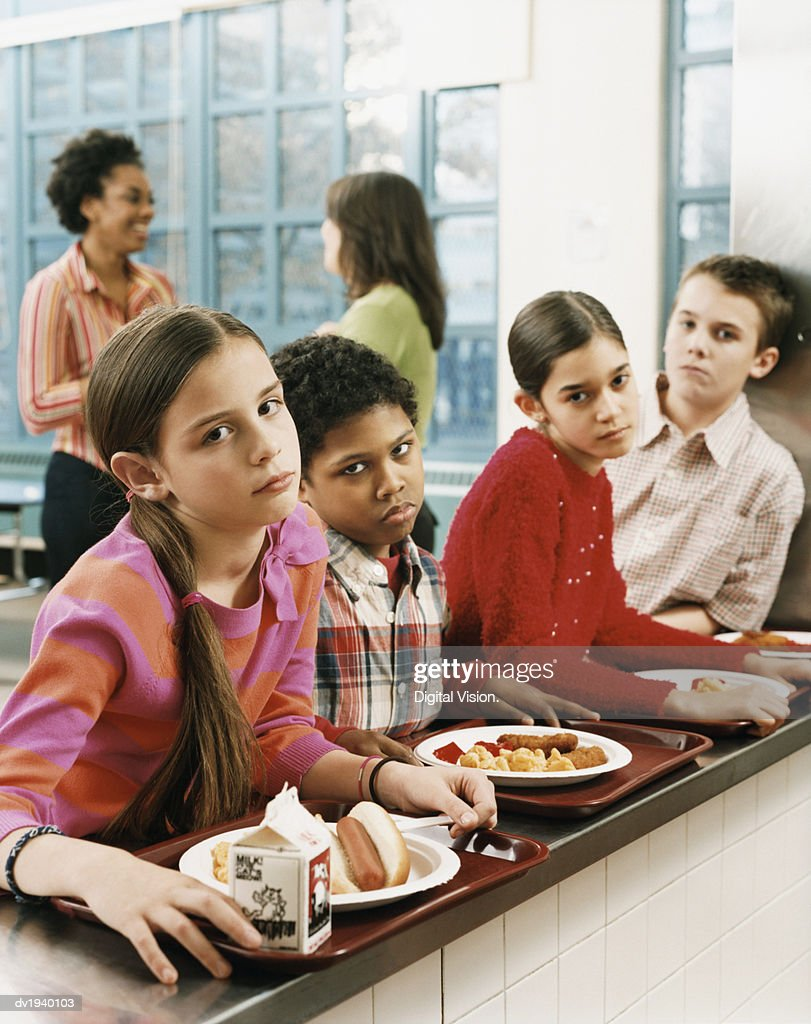 Four Schoolboys and Schoolgirls Looking Displeased With the Food on Their Trays : Stock Photo