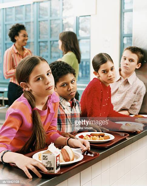 four schoolboys and schoolgirls looking displeased with the food on their trays - milk carton stock photos and pictures