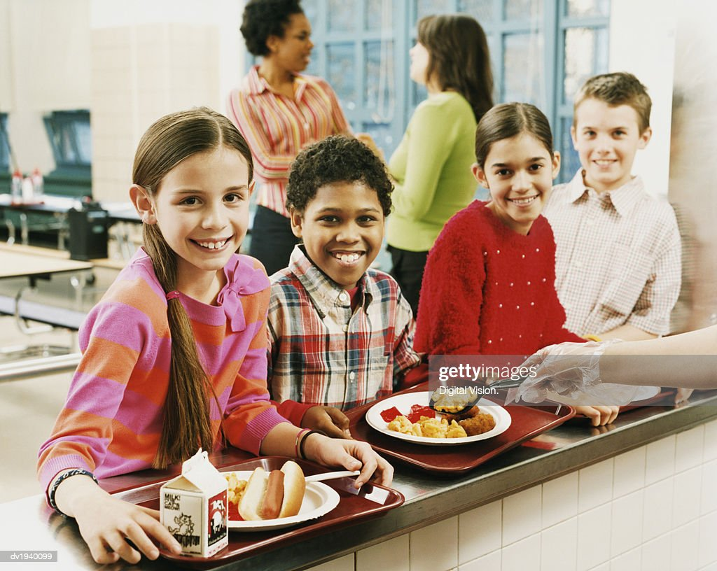 Four Schoolboys and Schoolgirls Queuing for Food, Two Women Talking in the Background : Stock Photo