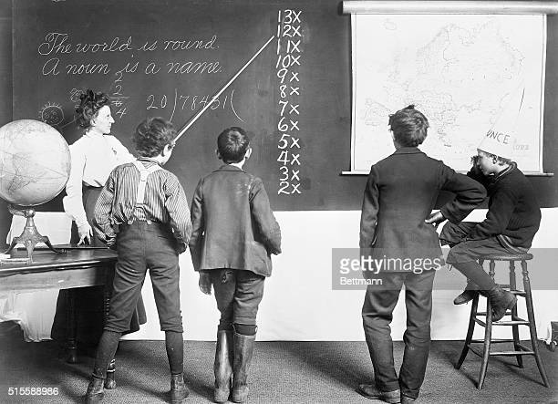 Four schoolboys watch as their teacher points to a lesson on the blackboard The boy on the right is sitting wearing a dunce cap