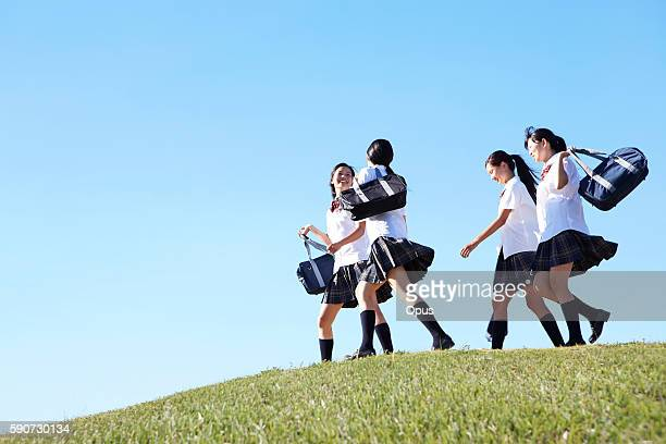 four schoolgirl on hill - female high school student stock pictures, royalty-free photos & images