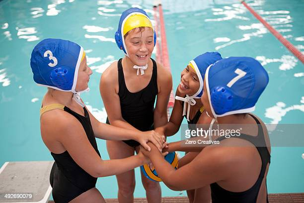 four schoolgirl water polo players holding hands poolside - water polo stock pictures, royalty-free photos & images