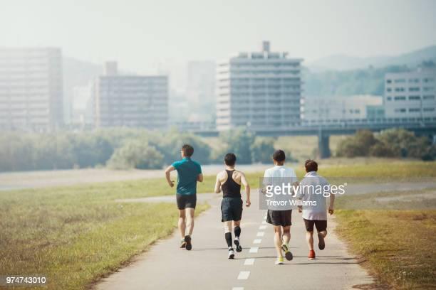four senior adults jogging together - 気が若い ストックフォトと画像