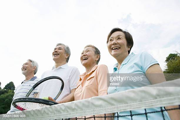 Four senior adults on tennis court, smiling, low angle view