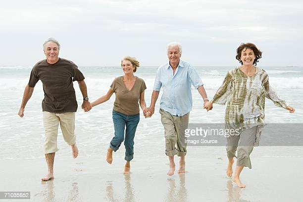 Cuatro adultos corriendo junto a senior en la playa
